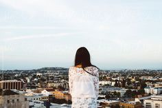 Let's go urban exploring. Young woman looking out toward a city.   Isaiah & Taylor Photography for Stocksy United