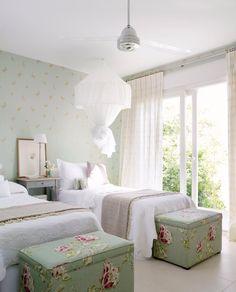 En este dormitorio, decorado por Casa y Campo, el verde aguamarina ha servido de nexo para coordinar el papel pintado y el tapizado de los pufs a pie de cama. A la hora de coordinar estampados siempre es importante que compartan el color base aunque los motivos sean distintos.