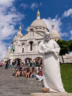 A street artist performs in front of the Basilica of the Sacre Coeur on the Montmartre hill in Paris.