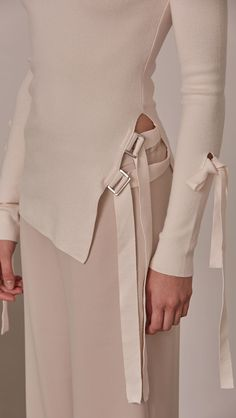 Daija Sweater in Ivory. The slim-cut with lightning slashes cutting through shoulder and creating a flattering buckle opening along side. Self-tied strap on sleeves. Super soft feel. Designed to skim the body.