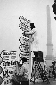 Workmen translate direction signs from French to German at the Place de la Concorde during the Nazi occupation of Paris.