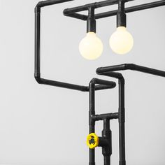 Fun design floor lamp made of pipes. Here with creative and playful knob dimmer in yellow color and two milk globe bulbs.