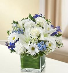 Healing Tears - Blue and White Arrangement The freshest roses, delphinium, lilies, daisy poms and carnations are hand-designed in a stunning cube vase, equally perfect as a gesture of comfort and peac