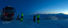 Nature's Own Balcony View of Longyearbyen - A tracked vehicle has brought a group of Svalbard tourists on top of a mountain this cold February evening for a splendid panorama view of Longyearbyen and its surrounding snow-covered mountains at dusk.