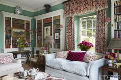 In Penny Morrison's Welsh home, the library's sofa is upholstered in a linen by Romo, the cushions are covered in embroidered Turkish fabrics, and the portrait of the Morrisons' son, Ted, is by Lucy P. Kent; the curtains are of a linen print by Penny Morrison Fabrics, and the walls are painted in Farrow & Ball's Arsenic.   - ELLEDecor.com