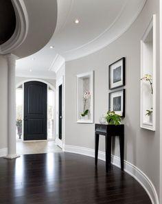 moldings | elegant living space | round hall | black and white color scheme | black door | dark wood floor