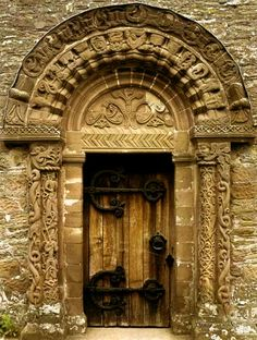 Ornate entry and door with enormous hinges.