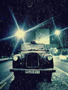 A black cab on a snowy London night.