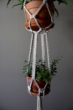 This long, sturdy macrame plant hanger is handmade with 5mm natural white cotton rope, featuring four thick knotted strands, hung by a small brass