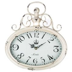 "How beautiful is this Antique Cream Oval Metal Wall Clock with Top Swirl? Only time will tell! Featuring a gorgeous, shabby-chic shade of antique cream, along with a glass-covered marbled gray-toned face and a pretty swirl detail at the top, this beautiful clock will serve as both a functional accent and a decorative touch in your home or office. Dimensions: Length: 12 1/2"" Width: 11"" Thickness: 2"" Hanging Hardware: ..."