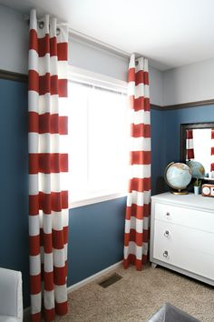 "Lowered trim piece, brings the ceiling color down onto the walls (also a ""dipped"" effect), striped red curtains"