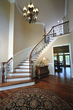 White wainscoting going up the wood and white staircase with black iron spindles makes for an elegant touch to a traditionally decorated entryway.