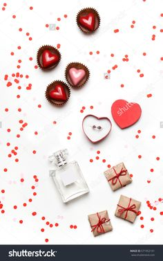 Styled Valentine's Day flatlay top view isolated on white. Sweet hearts, gifts in craft paper, proposal ring in box, perfume and confetti. Party invitation or web ad template