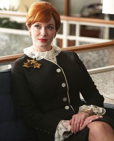 Joan Harris suited up in a sharp shaped jacket and skirt. A leaf motif brooch and a lace blouse peeking out from her suit jacket added a dose of femininity to her look.