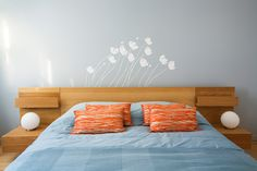 Modern bedroom with Ikea Malm bed, cool orange throw pillows and wall decal