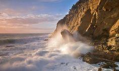 golven slaan tegen een ruige kust..