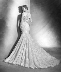 VAREL style: Sexy mermaid wedding dress in Chantilly lace and rebrodé lace with guipure appliqués. Bodice with round neck and scalloped edge and long sleeves. All-over sheer effect dress. Imposing mermaid skirt.