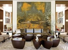 An Anselm Kiefer landscape overlooks the living room's Christian Liaigre sofa (in a Kravet velvet) and Wendell Castle low tables, one of which is topped by Louise Hindsgavl figurines   archdigest.com