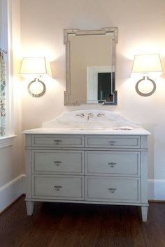 Elegant bathroom features antique gray washstand topped paired with white marble countertop and curved marble backsplash adorned with faucet under fretwork mirror illuminated by Large Ring Wall Sconces.