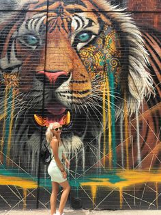 Woman in white tank top and blue denim jeans standing beside lion wall graffiti Tiger Face Paints, Bodybuilding Meal Plan, Coffee Maker With Grinder, Buying New Car, Netflix Gift, Sweet Cocktails, Instagram Giveaway, White Tank, Image Shows