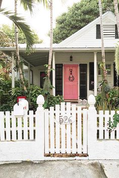 Palm trees and picket fences have nothing on that watermelon-tinted door. #frontdoor #pinkdoors #colorfuldoors #southernliving
