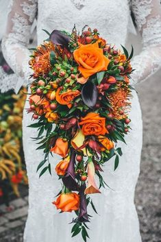 cascading wedding fall bouquet with purple and orange flowers