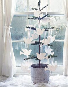 "Peace on Earth:   Pure white doves flock en masse to the miniature tree's branches, proclaiming ""peace on Earth."" Cut your own from white card stock and hang from lengths of ribbon, or use dove-shaped gift tags for a quicker solution. In keeping with the humble theme, the tree sits inside a pale blue-painted galvanized bucket.  Photo Credit: Keith Scott Morton"