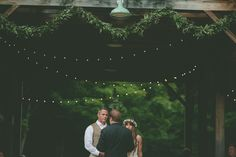 Love the green garlands and bistro lights. Meredith & Rob on Borrowed & Blue.  Photo Credit: The Pinwheel Collective