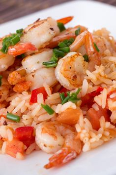 Recipe including course(s): Entrée; and ingredients: cajun seasoning, extra-virgin olive oil, fresh parsley, garlic, kosher salt, lemon, pepper, plum tomato, scallion, shrimp , unsalted butter, water, white rice