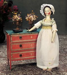 """French 18th Century Doll Furniture w Original Finish w Urns of Silk Flowers. 10"""" (25 cm.) w. x 8""""h. Original faded-red painted finish with cream edging,painted cream faux-key-holes,brass knobs with pull-rings,and a faux-marble green finished top. Arranged on the chest is a pair of early gilded metal double-handled urns with wooden bases,each with an arrangement of early silk flowers. Excellent condition. Pencil noted on the bottom is """"don de M. Gautier 1916,Cet objet date de 1750""""."""
