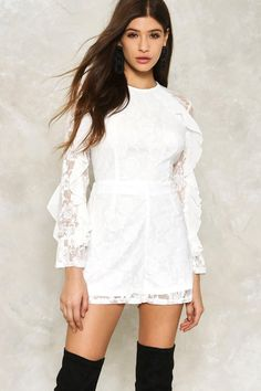 Because dresses are overrated. The Tess romper comes in lace with rose details and features a high neckline, mini silhouette, sheer inserts to the sleeves and back, zip closure at back, and long sleeves with ruffle detailing. Wear it with over-the-knee boots.