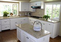 Dark wood, white cabinets, tannish walls, granite countertops, and oil rubbed bronze hardware