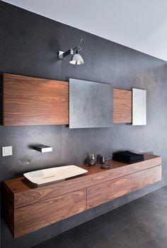un meuble de salle de bain en bois et des murs gris