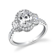 Style# SY596S Classic Oval Three-Stone Diamond Engagement Ring - This elegant and classic three-stone diamond engagement ring features a stunning 2 carat oval diamond center inside a halo of shimmering pave diamonds. On each side, a sparkling baguette diamond, also nestled in a halo of diamonds, gracefully accents the center stone, and a trail of more diamonds line the white gold shank. https://www.sylviecollection.com/classic-oval-three-stone-diamond-engagement-ring-sy596s