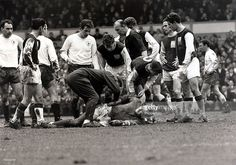 16th April 1966, White Hart Lane, London, England, League Division One, Tottenham Hotspur v Northampton Town, Northampton Town goalkeeper Bryan Harvey lies injured as team-mates and opposition, including Alan Mullery (white shirt, centre) look on
