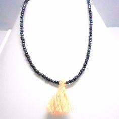 Long sautoir fantaisie composé de perles de rocailles rondes noires irisées et un pompon vieux rose pale