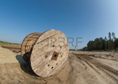 Electric wooden drum lying on a sand near the mine factory