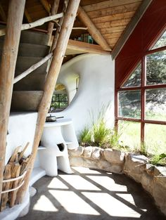 Gorgeous and sculptural cob stairs with angular timbers for supports that double as rail structure. Gaping south-facing windows help with solar heat gain, ability to grow plants and views.