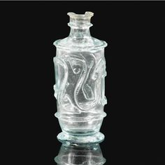 A Fatimid clear cut-glass bottle, Egypt or Syria, 10th-11th century of cylindrical form on a short spreading foot, with a narrow neck and everted rim, gently sloping shoulders leading to the body decorated with two relief-cut curved and etched vine scrolls with upward and downward-pointing palmette terminals 6.5cm. height