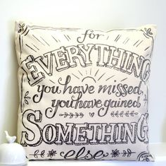 "A natural coloured, cotton canvas cushion with black text.A gorgeous, natural cotton canvas cushion with a beautiful saying printed into it in a mix of vintage style types in grey print, The cushion say's ""for everything you have missed you have gained something else"". The saying is framed in a pretty printed border and the design also includes flower detail. This cushion is a lovely addition to your bedroom or living room and would make a really nice gift too.Cotton canvas cover. Polyester…"