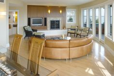 A curving couch takes advantage of the shape of this house, which is on a lot shaped like a slice of pizza. The shape gave the architects an excuse to build a more modern-looking home than the typical New England-style beach properties nearby.