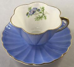 "Shelley Periwinkle Blue Teacup and Saucer, Dainty Style #0472 Truly a beautiful Shelley set in a striking Periwinkle Blue! Shelley Collector Find All gold handle Gold gilt handle Measures Cup opening 3.5"" Including handle 4"" Saucer 5.7"" *Combined Shipping is Available for"