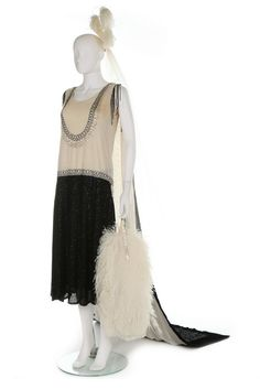 A Reville Ltd of Paris couture court dress and train, circa 1928, labelled Reville Ltd, and with inscribed ribbon label 'Lady Holcroft', the extensively beaded flapper-style dress in black and white seed beads with clear droplet beads, the bodice and waist defined by rhinestone studded bands, the matching train in dramatic black and white with foliate bands, edged in black velvet, bust 86-92cm, 34-36in; together with court presentation plumes and veils and an ostrich feather fan.