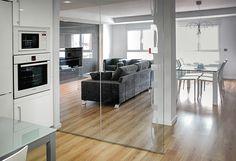 Chiralt Arquitectos I Cristalera separadora Salón-comedor de cocina en vivienda moderna acabada con deslumbrante suelo de parquet.