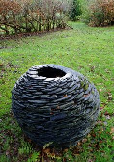 sculpture slate swirling urn-- substitute the bottom of glass soda bottles. Then put a candle inside.
