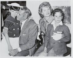 Meet a very happy family. Stars of the 'I Love Lucy' television series, Desi Arnaz and flame-haired wife Lucille Ball, who have been married happily for 19 years, display their affection for their children, Desi Jr., aged 6, and Lucie, aged 8, at a Savoy Hotel press conference, after their arrival in London. Lucille and Desi will be seen in a new 'I Love Lucy' series on Associated Redifussion next Friday.