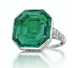 An Art Deco Emerald & Diamond Ring by Cartier.Bezel-set with an octagonal-shaped emerald, to the single and old-cut diamond three-row gallery and shoulders, , mounted in platinum . Accompanied by report no. CS 1079646 dated 31 October 2016 from the AGL American Gemological Laboratories stating that it is the opinion of the Laboratory that the origin of this emerald would be classified as Colombia, with insignificant clarity enhancement, traditional type