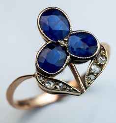 An Antique Russian Blue Sapphire and Rose Cut Diamond Flower Ring, St. Petersburg, 1904-1908. The rose gold ring is designed as an Art Nouveau flower set with natural sapphires and old rose cut diamonds. The ring is marked with 56 zolotnik gold standard with assayer's initials of Alexander Romanov.