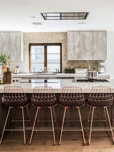 This gorgeous kitchen in greys and copper (our favorite metal of the year) with warm woods has a rustic, yet modern vibe that we love.