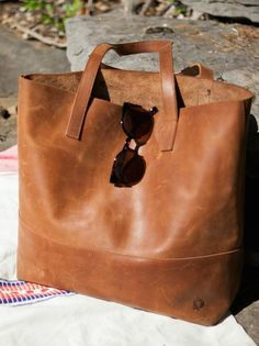 "Hand crafted in Ethiopia // 100% Ethiopian leather Includes detachable leather pouch, with snap closure. MADE BY FASHIONABLE PRODUCTS GREAT.LY is proud to have Fashionable as one of our makers! They work with women in Africa to create gorgeous pieces (bracelets, scarves, bags) ""to create sustainable business for Africans so they aren't dependent upon charity, but instead earn the dignity of a job. We offer opportunity to everyone, with a primary focus on empowering women.""  Amazing"